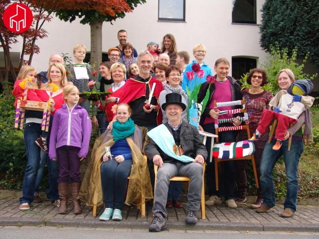 Theodor-Hürth-Straße (2/4): Eine erprobte Straßenfestgemeinschaft mit Kaiser, König und Königin, Rosenbogen und wunderschöner Beflaggung. Die Besonderheit in diesem Jahr rankt sich um den Symbolträger des Tags der Nachbarschaften: Jede teilnehmende Familie bastelt einen bunten Stuhl!
